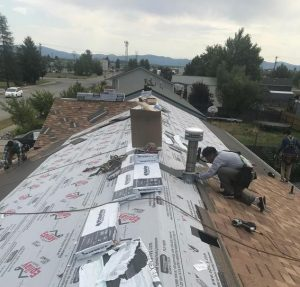 Roofing Contractors installing asphalt composition shingles on residential Roof