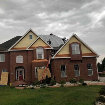 Roofing contractors installing asphalt composition shingles on two-story residential roof