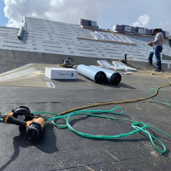 Roofing contractors installing ice and water shield and felt on residential roof